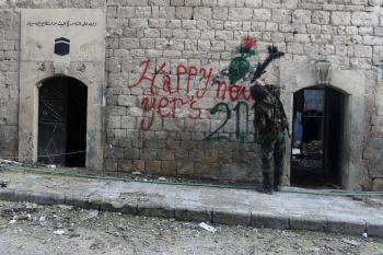 أحد أفراد الجيش السوري الحر يكتب تحية بالعام الجديد قرب مدينة حماه التي دمرتها الحرب