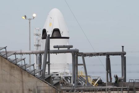 عامل يقف بجوار مركبة سبيس إكس في محطة كيب كنافيرال الجوية في فلوريدا يوم الخامس من مايو .
