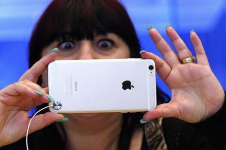 صورة لامرأة تحاول التقاط صورة بهاتف آيفون 6 بلس في متجر أبل في سيدني
