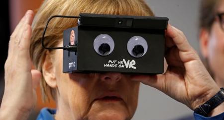 المستشارة الألمانية أنجيلا ميركل تجرب نظارة واقع افتراضي في معرض بهانوفر يوم 25 أبريل 2016