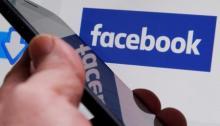 صورة لرجل يمسك هاتفا محمولا وأمامه شعار شركة فيسبوك في فرنسا