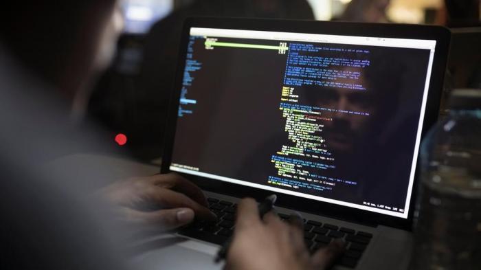 إنعكاس لصورة احد القراصنة وهو يكتب الكود الخاص بعملية هجوم إلكتروني