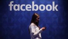 امرأة تستخدم الموبايل تحت شعار فيسبوك، تعمل عملاق الشبكات الاجتماعية على تقييد الأشخاص الذين خالفوا بعض القواعد من استخدام خدمة البث المباشر ، رداً على هجوم المسجد الإرهابي في كرايستشيرش ، نيوزيلندا