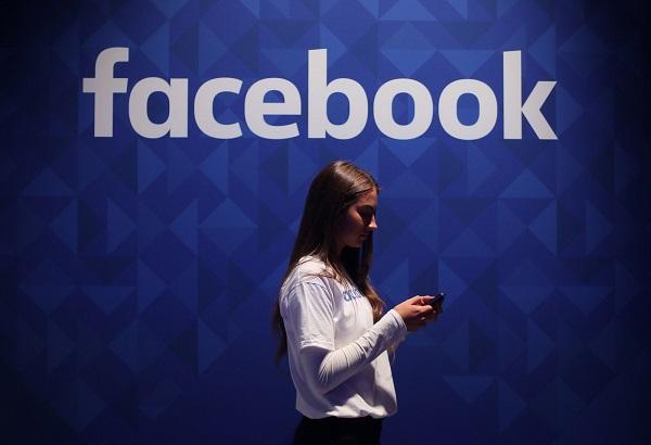 امرأة تستخدم الموبايل تحت شعار فيسبوك، تعمل عملاق الشبكات الاجتماعية على تقييد الأشخاص الذين خالفوا بعض القواعد من استخدام خدمة البث المباشر