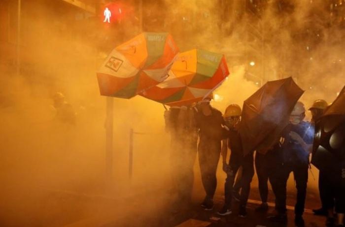 محتجون مؤيدون للديمقراطية يحتمون من الغاز المسيل للدموع بمظلات في هونج كونج يوم 28 يوليو 2019.