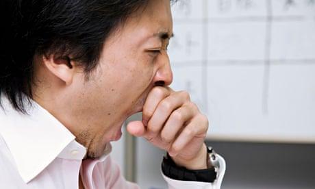 رجل يتثاءب في المكتب. شعر 54٪ فقط من المشاركين اليابانيين في استطلاع رأي بأنهم ينامون نوما هنيئا كل يوم