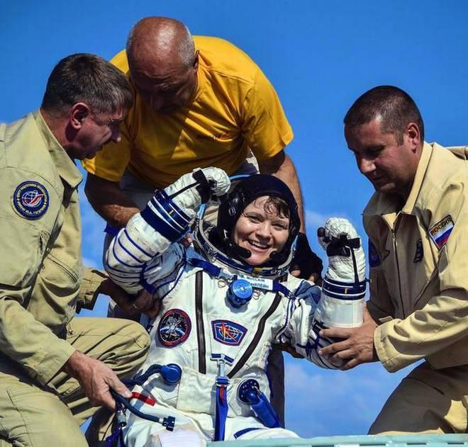 أشخاص يساعدون رائدة الفضاء، آن مكلين، لدى عودتها من محطة الفضاء الدولية في يونيو الماضي