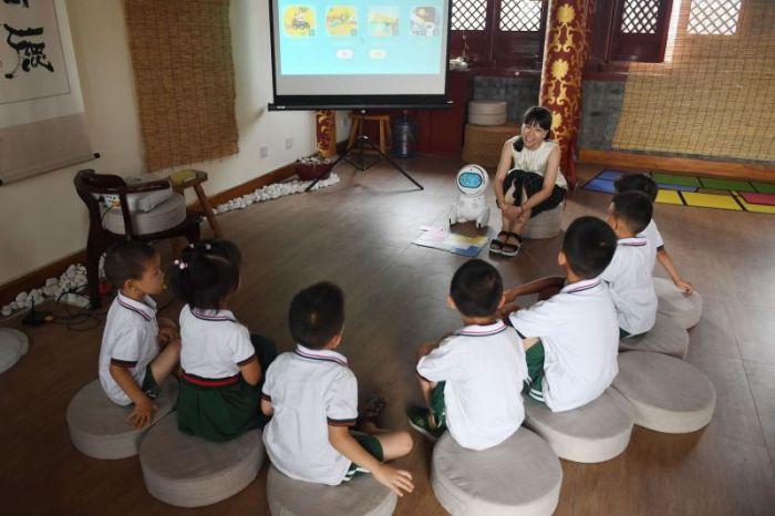 أحد المعلمين يقدم روبوت Keeko للأطفال في معهد Yiswind للتعليم متعدد الثقافات في بكين في 30 يوليو 2018