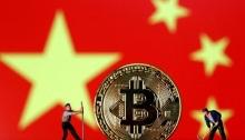 تماثيل لعب صغيرة بجانب صورة عملة بتكوين الافتراضية المعروضة أمام العلم الصيني في صورة توضيحية بتاريخ 9 أبريل 2019
