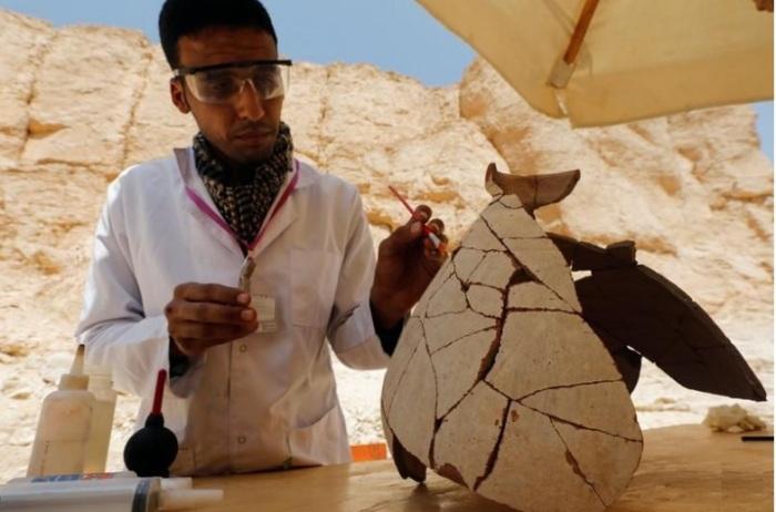 خبير مصري يعمل على ترميم قطعة أثرية في الأقصر يوم الخميس 10 أكتوبر 2019