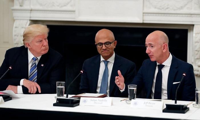 الرئيس التنفيذي لشركة مايكروسوفت ساتيا ناديلا يجلس بين دونالد ترامب وجيف بيزوس في اجتماع بالبيت الأبيض عام 2018