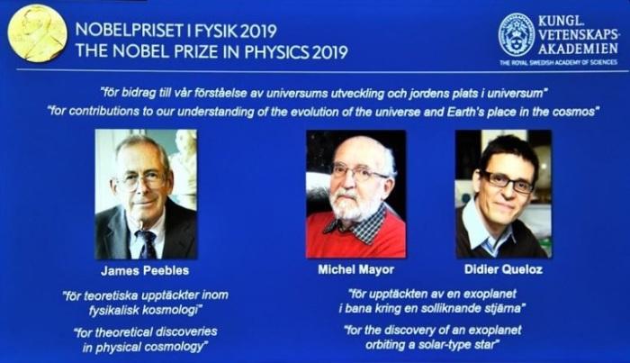 شاشة تعرض صور للعلماء الفائزين بجائزة نوبل للفيزياء لعام 2019 وهم (من اليسار إلى اليمين) جيمس بيبلز وميشيل مايور وديدييه كويلو خلال مؤتمر صحفي في ستوكهولم يوم الثلاثاء 8 أكتوبر 2019