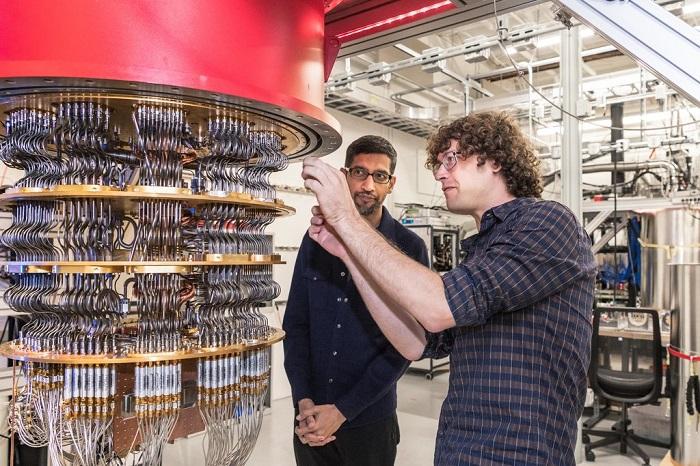 سوندار بيشاي الرئيس التنفيذي لشركة جوجل (يسار) وباحث من الشركة يختبر الكمبيوتر الكمي