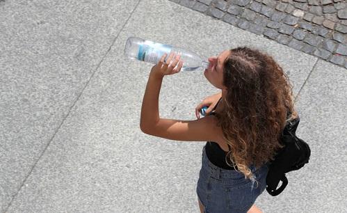 امرأة تشرب المياه المعبأة في زجاجات خلال الطقس الحار في برلين في يوليو 2019