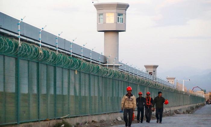 عمال يمشون بالقرب من السياج المحيط لما يعرف رسمياً باسم مركز تعليم المهارات المهنية في شينجيانج
