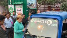 المستشارة الألمانية أنجيلا ميركل تقف بجانب سيارة كهربائية في الهند يوم 2 نوفمبر 2019