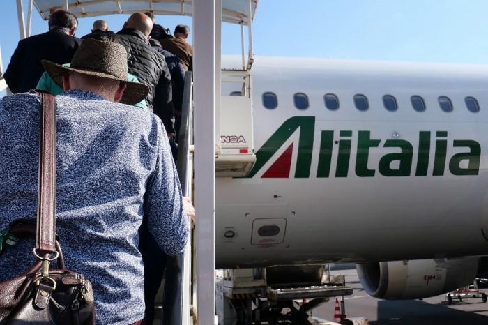 مسافرون يصعدون الي طئرة أليطاليا من مطار روما الدولي