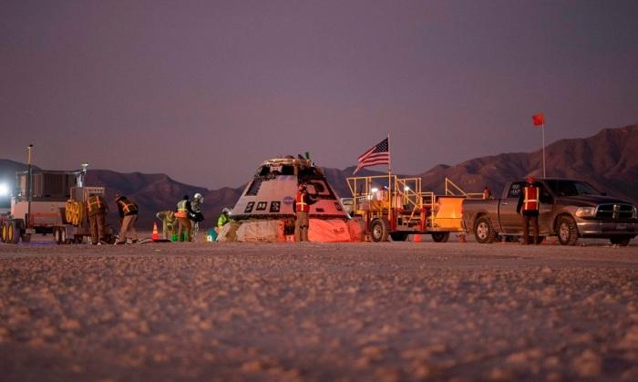 خبراء من بوينج وناسا والجيش الأمريكي يحيطون بمركبة الفضاء ستارلاينر من شركة بوينج بعد وقت قصير من هبوطها في وايت ساندز، بصحراء نيو مكسيكو