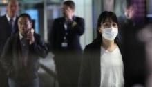 امراة تضع كمامة لدى وصولها إلى مطار كولالمبور الدولي يوم 21 يناير 2020