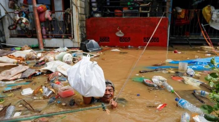رجل يمسك بحبل وهو يوزع الطعام في منطقة متأثرة بالفيضانات بعد هطول أمطار غزيرة في جاكرتا ، إندونيسيا ، 2 يناير 2020