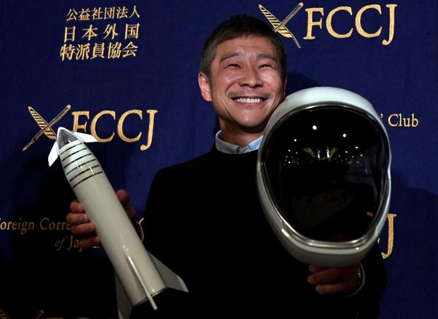 يوساكو مايزاوا ، رجل الأعمال والرئيس التنفيذي لشركة زوزو تاون للأزياء وأول راكب خاص لشركة سبيس إكس، يمسك بصاروخ مصغر وخوذة فضائية قبل مؤتمر صحفي في نادي المراسلين الأجانب في اليابان في طوكيو في 9 أكتوبر 2018