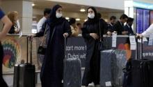 مسافرون يضعون كمامات على وجوههم في مطار دبي الدولي يوم 29 يناير 2020