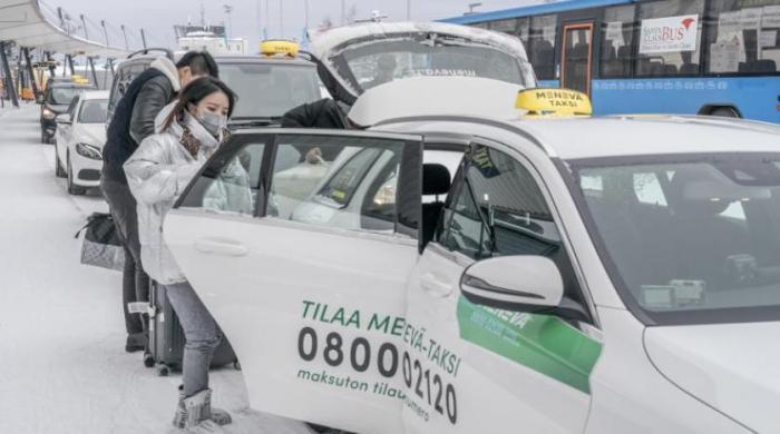 سائحان صينيان يضعان قناعين واقيين بعد وصولهما إلى مطار روفانييمي في فنلندا خوفا من فيروس كورونا