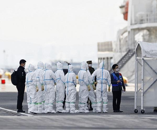 """ينتظر المسؤولون الذين يرتدون بدلات واقية يوم الجمعة 6 فبراير بجانب السفينة السياحية """"أميرة الألماس"""" الرابطة في ميناء دايوكو في يوكوهاما، حيث ثبتت إصابة 41 شخصًا آخرين بفيروس كورونا الجديد"""