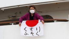 أحدي المسافرات علي سفينة أميرة الألماس تمسك بالعلم الياباني وتضع كمامة خوفا من وصول الفيروس المتفشي في السفينة إليها