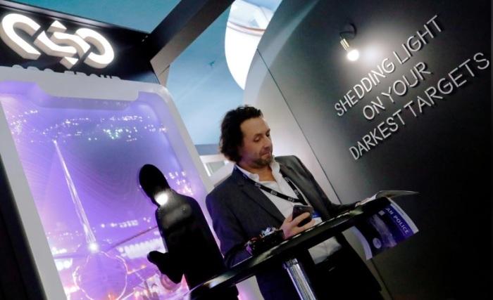 رجل يقرأ في كتيب في جناح شركة NSO Group Technologies، وهي شركة تكنولوجيا إسرائيلية معروفة ببرنامج التجسس Pegasus الذي يتيح المراقبة عن بعد للموبيلات الذكية، وذلك في مؤتمر الشرطة الأوروبية السنوي في برلين، ألمانيا، 4 فبراير2020
