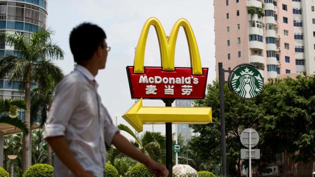 أحد المشاة يمشي بجوار لافتات ماكدونالدز وستاربكس في حي فوتيان في شنتشن، الصين
