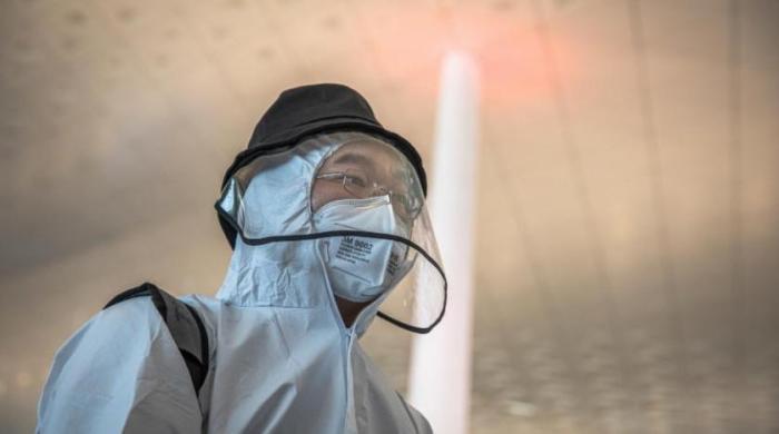شخص يرتدى قناع وجه أثناء انتظاره في مطار ووهان تيانخه الدولي بعد رفع الإغلاق عن المدينة
