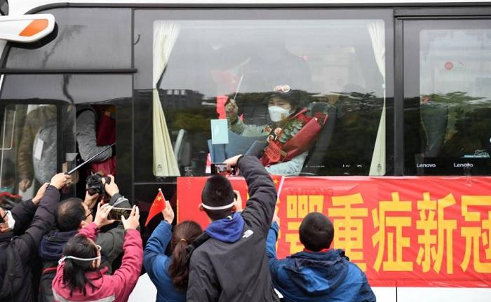 لي لانجوان، عالمة الأوبئة في كلية الطب بجامعة تشجيانج، تلوح بعلم صيني من داخل حافلة أثناء مغادرتها ووهان، مقاطعة هوبي، مركز تفشي مرض فيروس كورونا في الصين (كوفيد-19) ، 31 مارس 2020