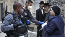 ضباط شرطة إسرائيليون يرتدون قفازات واقية وأقنعة يفحصون الأوراق وهم يفرضون قيودًا في حي يهودي متشدد في القدس يوم الثلاثاء 31 مارس، خلال إغلاق جزئي للحد من انتشار عدوى فيروسات كورونا
