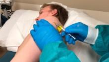 أحد المشاركين في تجربة لقاح فيروس كورونا كوفيد-19 ، يتلقى حقنًا في مدينة كانساس سيتي، بولاية ميزوري الأمريكية. اللقاح تم تطويره عن طريق شركة إنوفي للأدوية، 8 أبريل 2020