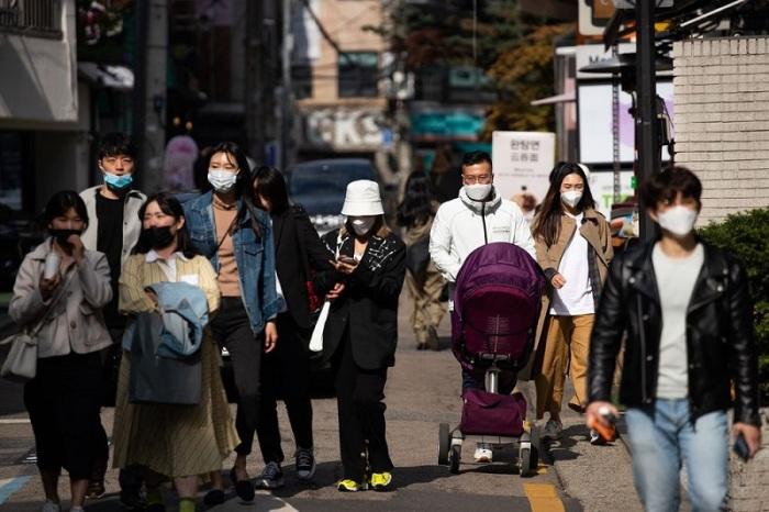 """يسير الكوريون في حي """"جاروسو جيل"""" بمنطقة جانجنام في سول كوريا الجنوبية، يوم 18 أبريل 2020"""
