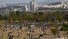 يجلس الكوريون في منتزه هان ريفر في سول عاصمة كوريا الجنوبية، يوم 18 أبريل 2020