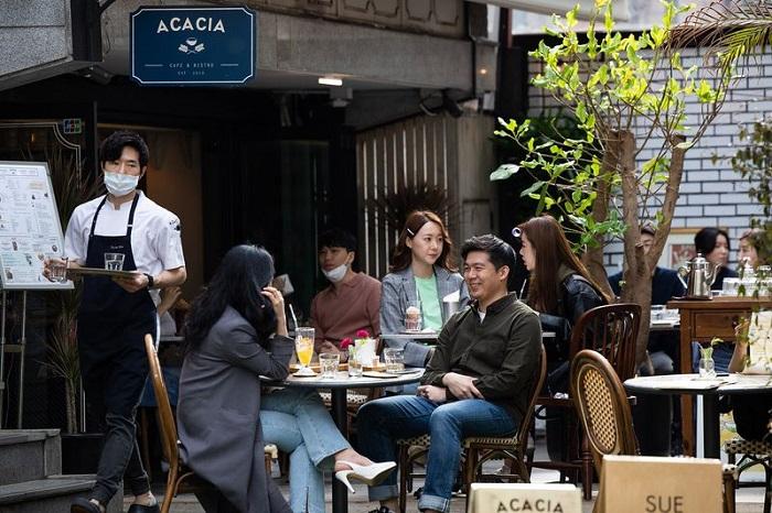 يجلس الكوريون في مقهى في حي جاروسو جيل في منطقة جانجنام في سول عاصمة كوريا الجنوبية يوم 18 أبريل 2020