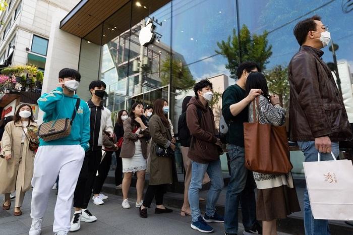 الناس ينتظرون في طابور خارج متجر شركة أبل في منطقة جانجنام في سول عاصمة كوريا الجنوبية، 18 أبريل 2020