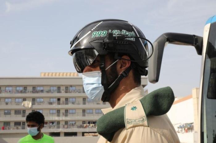 أحد أفراد قوات الشرطة الإماراتية يضع خوذة ذكية يمكنها قياس درجة حرارة مئات الأشخاص كل دقيقة في دبي يوم 23 أبريل 2020