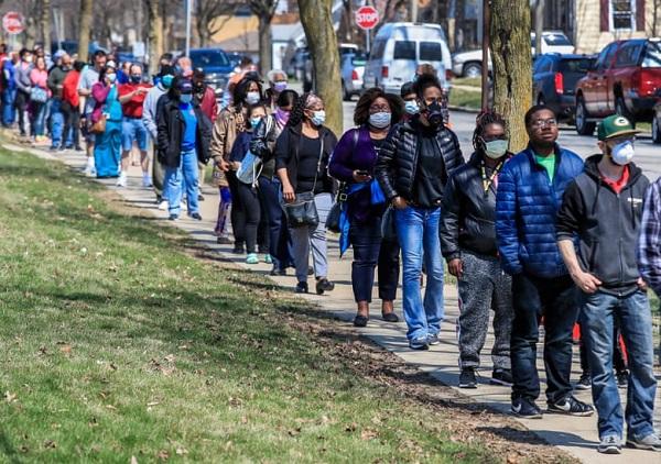 ينتظر الناخبون الأمريكيون للإدلاء بأصواتهم في الانتخابات الرئاسية الأولية في ولاية ويسكونسن، وهم يرادون أقنعة الوجه للوقاية من فيرةس كورونا