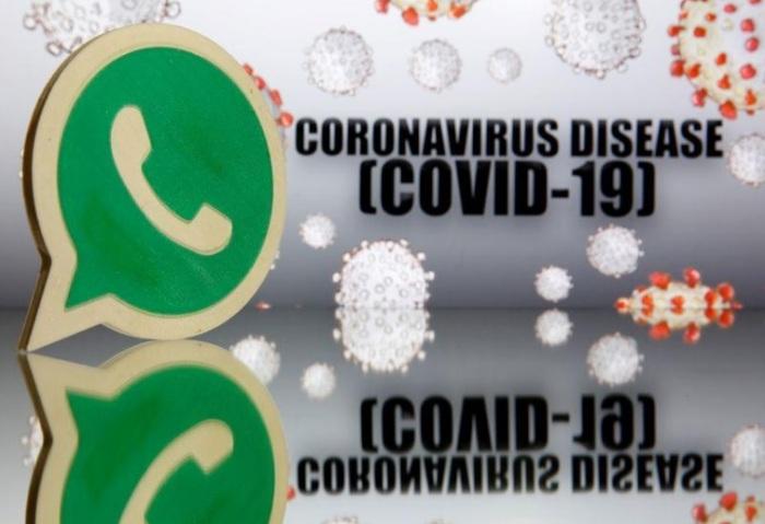 شعار تطبيق واتساب الذي تملكه شركة فيسبوك مطبوع بواسطة طابعة ثلاثية الأبعاد أمام علامة فيروس كورونا المستجد