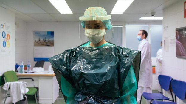 ممرضة للعناية المركزة في إسبانيا ترتدي كيس مهملات وقناع بلاستيكي وقائي، تبرعت به شركة محلية