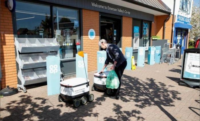 عامل يضع حقيبة داخل روبوت من شركة ستارشيب في ميلتون كينز بإنجلترا يوم 21 ابريل 2020