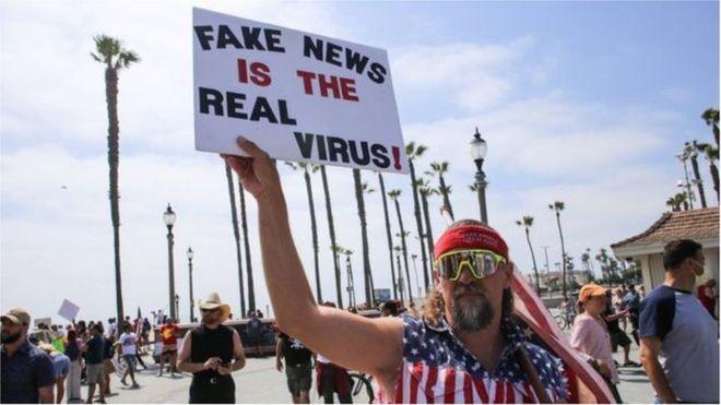 متظاهر يحمل لافتة تشكك في وجود فيروس كورونا في مظاهرة في كاليفورنيا