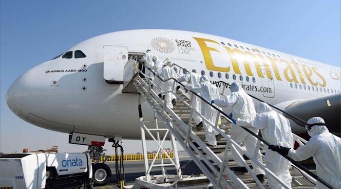 عمال نظافة يرتدون بدلات واقية يصعدون على متن طائرة تابعة لمجموعة الإمارات لتطهيرها في دبي يوم الخامس من مارس ٢٠٢٠