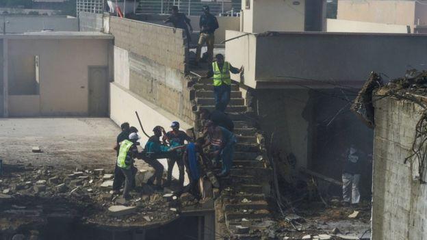 فرق الإنقاذ يقومون بإجلاء أحد ضحايا الطاشرة الباكستانية