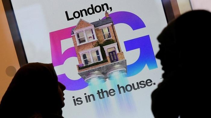 مشاة يمرون أمام إعلان يروج لشبكة بيانات الجيل الخامس البريطانية في متجر للهواتف المحمولة في لندن في 28 يناير2020