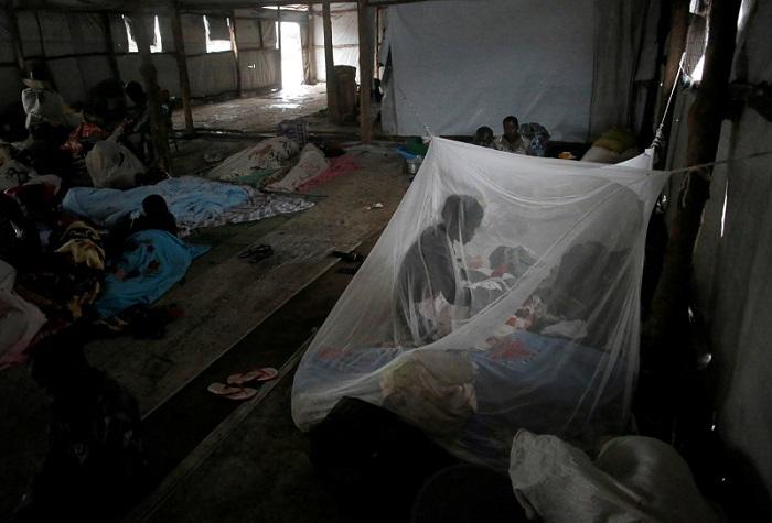 لاجئة من جنوب السودان تعتني بطفلها تحت ناموسية في خيمة مؤقتة في مخيم للاجئين في أوغندا عام 2017
