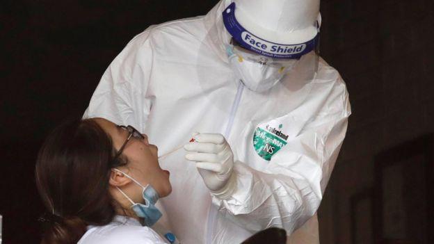 عنصر من الفرق الطبية يقوم بأخذ مسحة من مواطنة للكشف عن فيروس كورونا